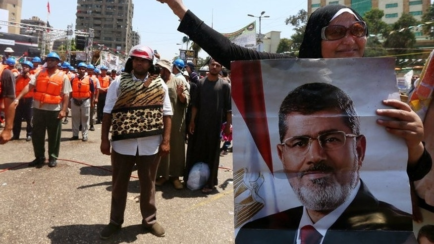 Egyptian supporters of the Muslim Brotherhood and ousted president Mohamed Morsi (on the poster) take part in self-defense training outside Rabaa al-Adawiya mosque on July 16, 2013 in Cairo. The European Union's top diplomat was heading for Cairo Wednesday, a day after an interim government was sworn in to replace Morsi, toppled by the military two weeks ago.