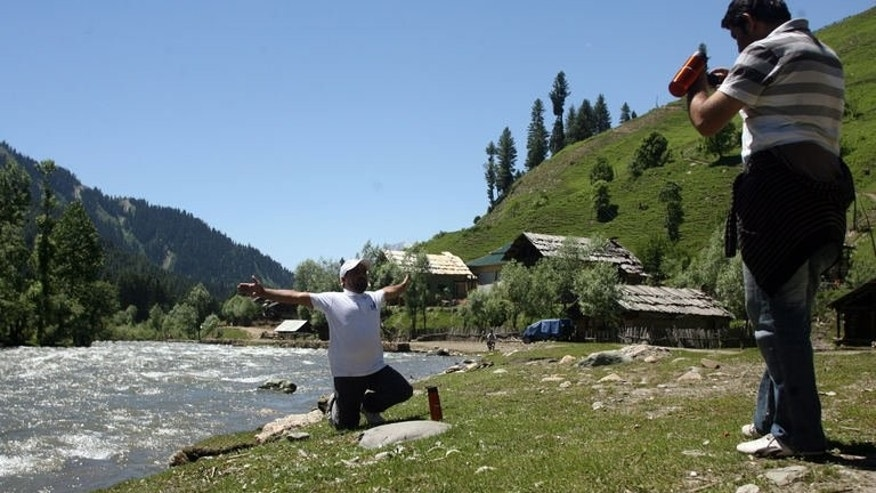 Tourists take photos next to Neelum river in the mountainous Neelum valley, in Pakistani controlled Kashmir, on June 9, 2013. Success stories can be rare in this country, but business is booming in a new holiday resort in Kashmir as the region rebuilds after a devastating earthquake and shrugs off associations with violence.
