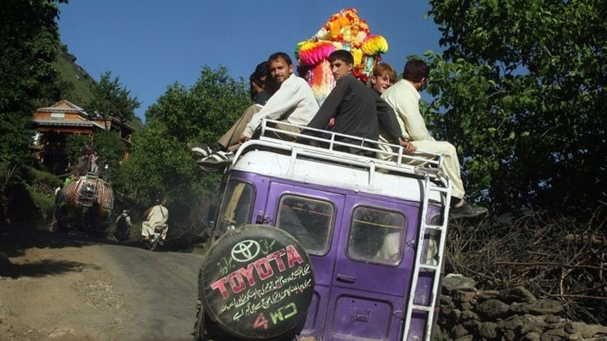 Tourists are seen travelling on the top of a vehicle in the mountainous Neelum valley, in the Pakistani controlled Kashmir, on June 8, 2013. Local tourism officials say 600,000 people visited Neelum last year compared to 130,000 in 2010.