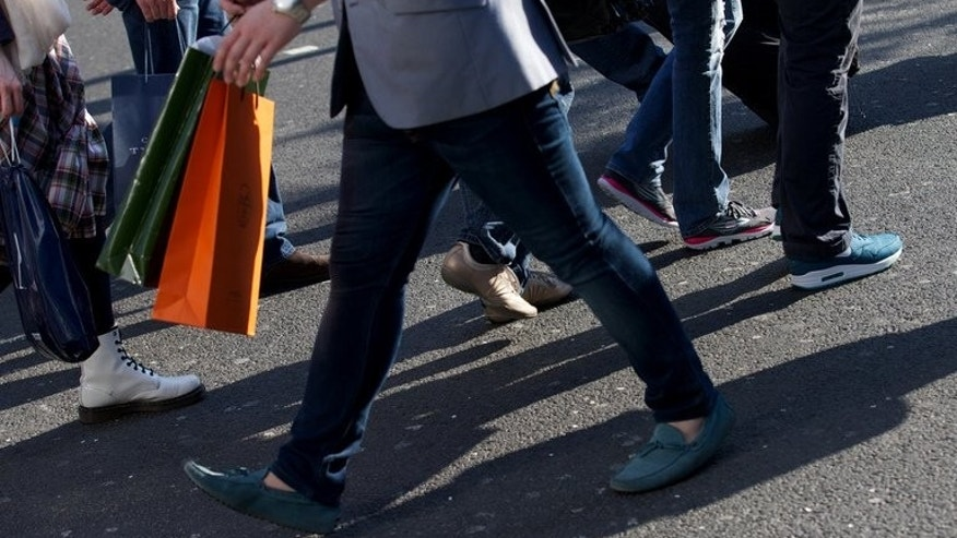 Shoppers walk along Oxford Street, in central London on April 25, 2013. British 12-month inflation jumped to 2.9 percent in June from a rate of 2.7 percent the previous month, official data shows.