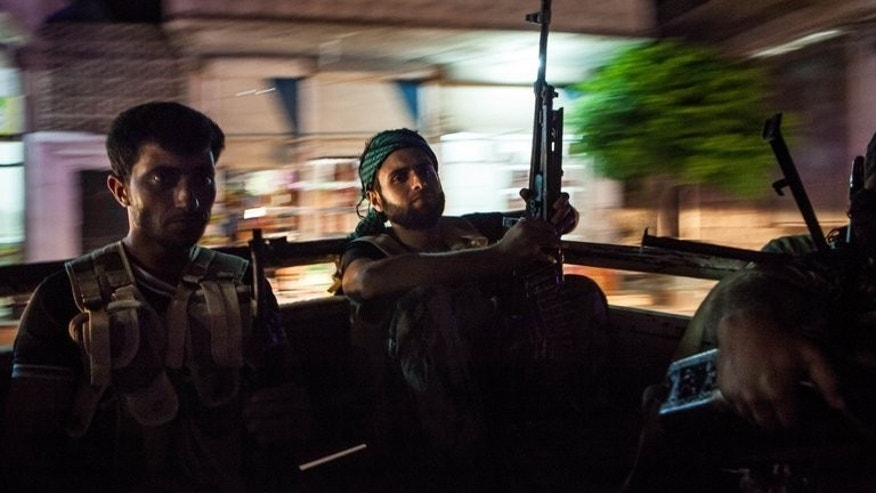 "Syrian rebels head to the town of Bsankol in the northwestern province of Idlib on July 11, 2013. Britain is to give Syrian opposition fighters equipment to protect them against chemical weapons attacks ""as a matter of special urgency"", Foreign Secretary William Hague said."
