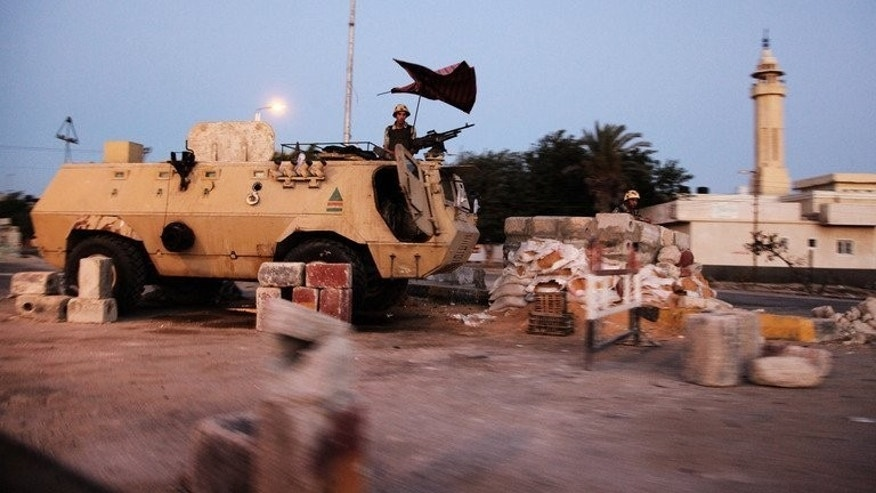 Egyptian soldiers stand on top of an armoured personnel carrier at a military checkpoint on the Egyptian side of the border town of Rafah, in the northern Sinai on August 10, 2012. Gunmen attacked an Egyptian army checkpoint in Rafah wounding eight people, security sources said Wednesday, as troops massed for an offensive against Islamist militants in the restive region.
