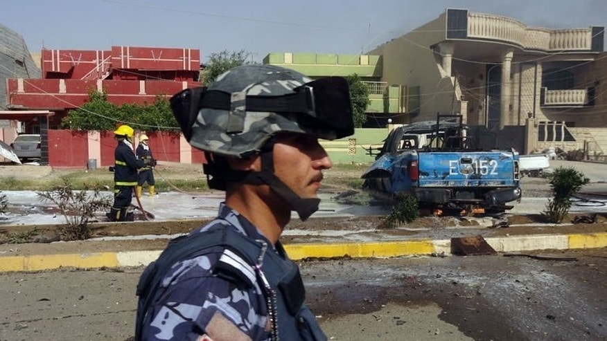 A policeman stands guard as a fire fighter extinguishes a blaze in Kirkuk, north of Baghdad on July 15, 2013, following an attack that killed an army lieutenant colonel and a soldier and wounded another. A bombing killed three children at a popular swimming area in Iraq on Wednesday, following a similar attack two days before, police and a doctor said.