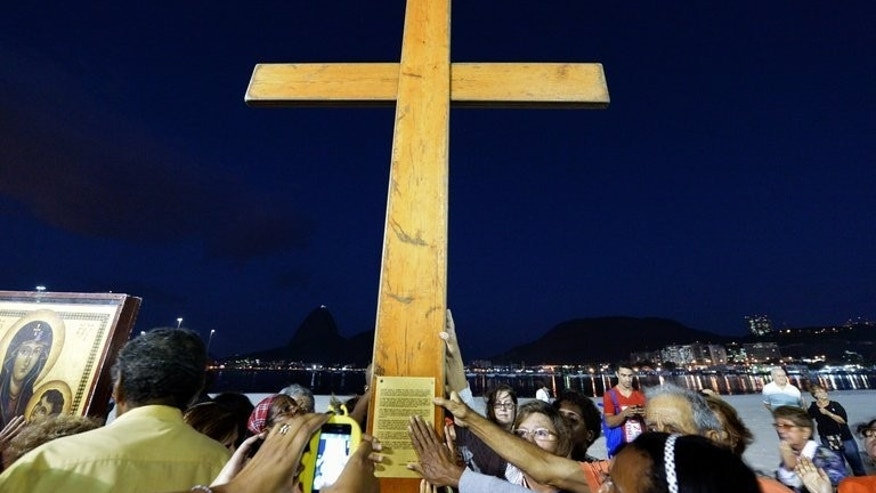 Catholics carry the World Youth Day cross at Botafogo beach in Rio de Janeiro, on July 15, 2013. Young Brazilians who marched in June to demand more funding for health and education are hoping Pope Francis will back their cause when he visits Rio next week.