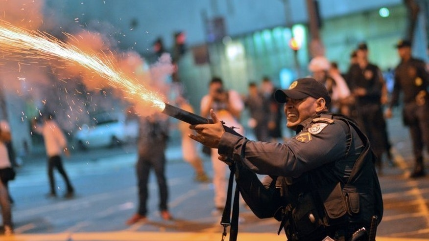 A Brazilian policeman fires tear gas at protesters after clashes erupted in Rio de Janeiro, on July 11, 2013. Young Brazilians who marched in June to demand more funding for health and education are hoping Pope Francis will back their cause when he visits Rio next week.