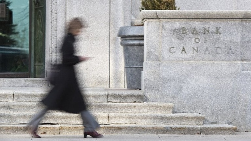A woman walks past the Bank of Canada building in Ottawa on April 12, 2011. Canada's central bank held its key interest rate at 1.0 percent, while downgrading its global economic forecast
