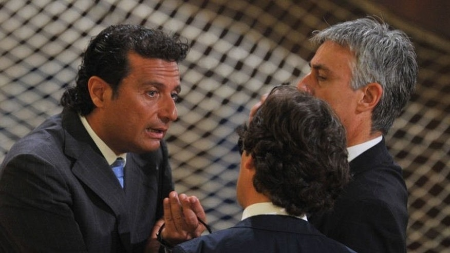 "Francesco Schettino (L), captain of the cruise ship Costa Concordia, speaks with officials before taking place for his trial in a local theatre in Grosseto, central Italy on July 17, 2013. Schettino's trial resumed on Wednesday, with the defendant dubbed ""Italy's most hated man"" facing 20 years in prison for a spectacular 2012 wreck in which 32 people lost their lives."