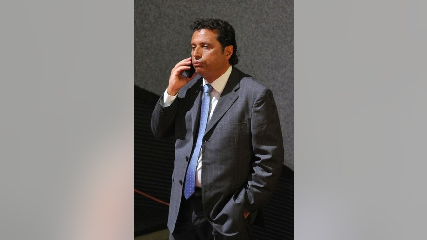 "Costa Concordia's captain Francesco Schettino speaks on his mobile phone before taking place for his trial in a local theatre in Grosseto, central Italy on July 17, 2013. Schettino's trial resumed on Wednesday, with the defendant dubbed ""Italy's most hated man"" facing 20 years in prison for a spectacular 2012 wreck in which 32 people lost their lives."