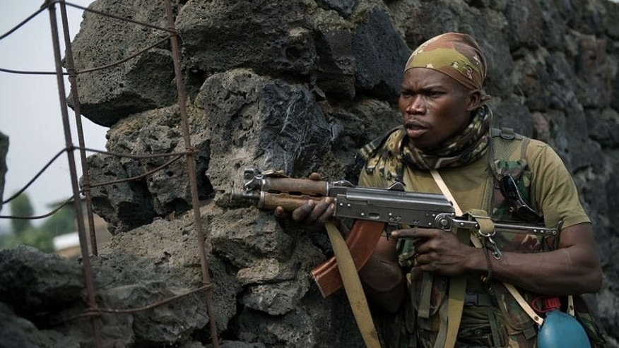 A Congolese army soldier takes position behind a wall during a fire-fight in Kanyarucinya, around 10km from Goma on July 17, 2013.