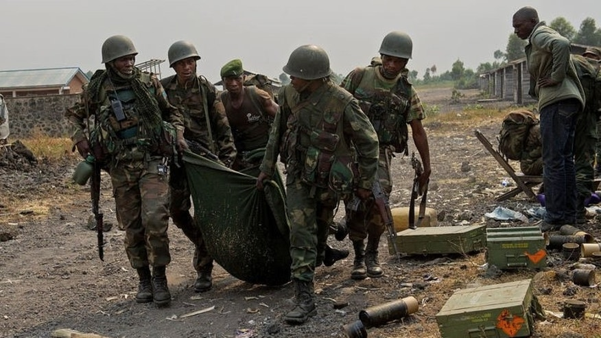 Congolese army soldiers carry the body of a comrade killed in fighting in Kanyarucinya, around 10km north of Goma, on July 17, 2013.