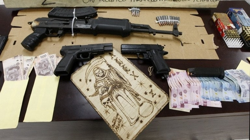 "An assault rifle, semiautomatic pistols, ammo and other stuff seized in the arrest of ten alleged members of the drug cartel ""Los Zetas"", are presented to the press in Monterrey, Mexico, on February 9, 2012. Honduran migrant Samuel Alberto Centeno Vazquez was approached to work for the Zetas drug cartel as he made his way along the railways that lead to Mexico's border with the United States."