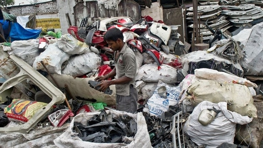 An Indian worker sorts items at a metal scrap market in New Delhi on July 17, 2013. With the Indian rupee depreciating by about 10 percent this year, scrap metal importers are halting fresh purchases on the concern of increasing raw material costs which they would be unable to onpass to the consumer.