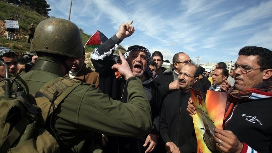 An Israeli soldier tries to break up Palestinian protestors as they demonstrate in the West Bank on February 15, 2013. New guidelines barring EU members from funding projects in Jewish settlements mean Israel must resume peace talks or risk isolation.