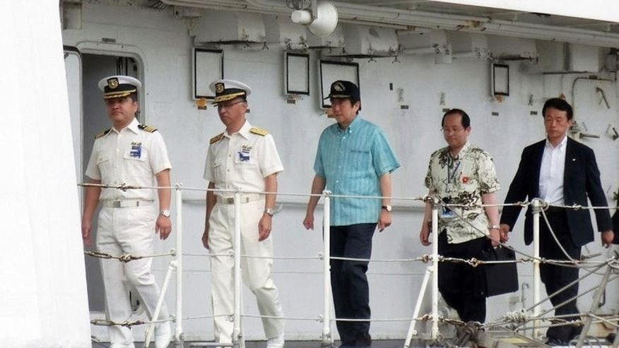 Japanese Prime Minister Shinzo Abe (C) inspects a Japan Coast Guard patrol boat off the remote Okinawan island of Ishigaki in the East China Sea, 2,000 kilometres (1,240 miles) southwest of Tokyo on July 17, 2013. Abe on Wednesday visited coastguards who patrol waters around islands at the centre of a dispute with China, as election campaigning stepped up a gear.