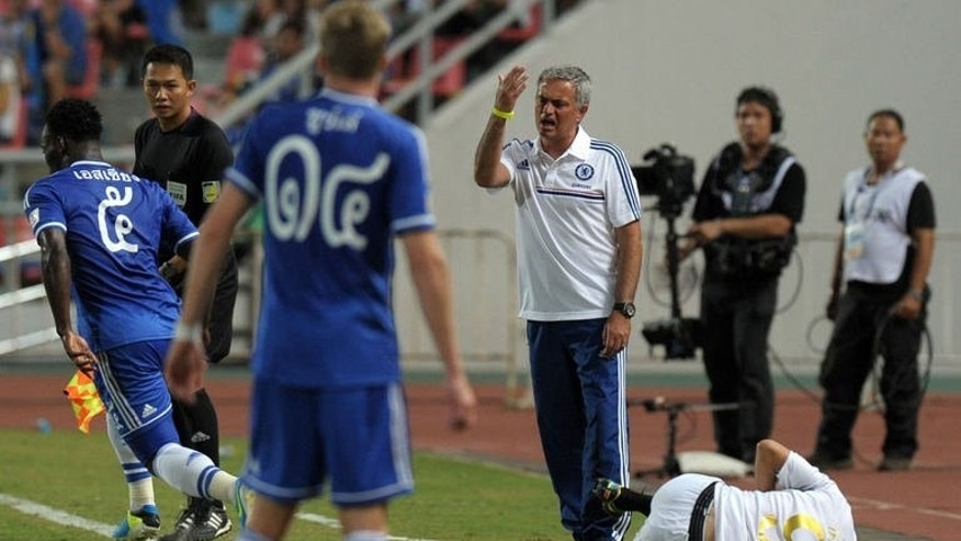 Chelsea football manager Jose Mourinho (C) gestures to his players as Cleiton Silva (R) of Singha All Star reacts during the exhibition match at Rajamangala National stadium in Bangkok on July 17, 2013. Chelsea beat Singha All Star 1-0.