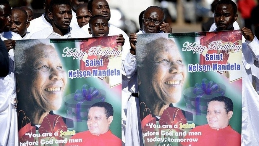 Members of the Brotherhood of the Cross and Star Christian church sing and hold tributes to Nelson Mandela outside his hospital in Pretoria on July 16, 2013. The former South African President is set to spend his 95th birthday in hospital Thursday, but across the world admirers hope to honour their icon's legacy through millions of acts of kindness.