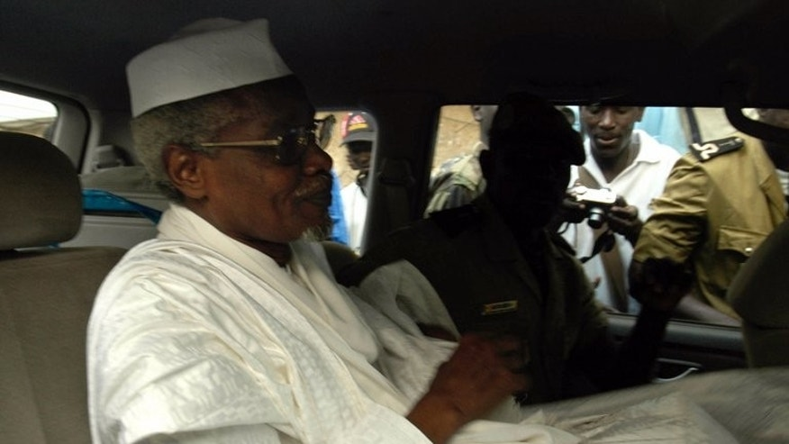 Chad's ex-dictator Hissene Habre leaves Dakar's courthouse escorted by prison guards on November 25, 2005. More than 1,000 alleged victims of Habre are suing him in Senegal, where he is being tried for genocide during his eight-year rule of Chad, their lawyers said on Wednesday.