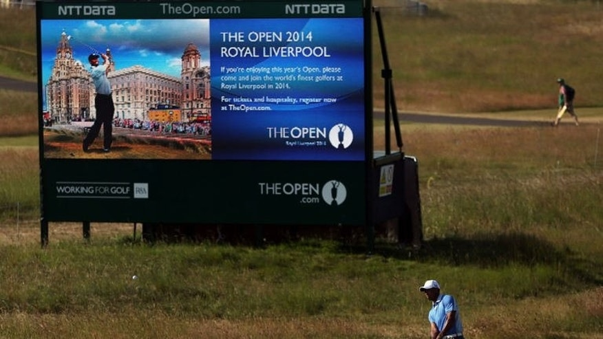 US golfer Tiger Woods plays a shot in front of a billboard advertising next year's championship during the last day of practice ahead of the 2013 British Open Golf Championship at Muirfield golf course at Gullane in Scotland on July 17, 2013.