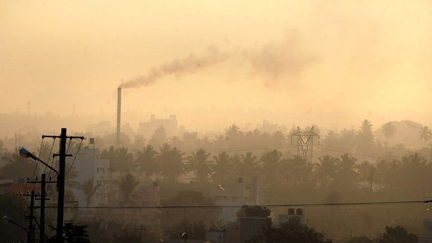 A factory chimney belches smoke in a residential area as haze casts a blanket over Bangalore, southern India on December 11, 2009. Pollution and other environmental degradation costs India $80 billion a year, nearly six percent of gross domestic product, the World Bank said in a report released on Wednesday.