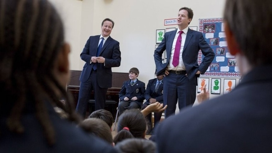 Prime Minister David Cameron (L) and Deputy PM Nick Clegg (R) visit a Brixton primary school, December 4, 2012. Primary school pupils could be ranked against their peers on a national scale under plans being championed by Clegg.