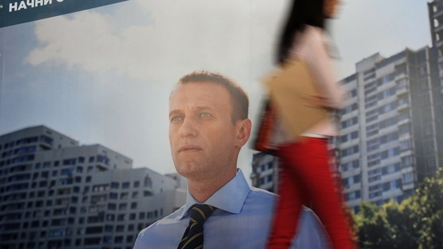 A girl walks past a billboard promoting Russian top opposition figure Alexei Navalny ahead of mayoral elections in Moscow, July 1, 2013. A Russian court will on Thursday deliver a verdict in the embezzlement trial of Navalny, an abrasive critic of President Vladimir Putin who risks years in prison and an end to his budding political career.