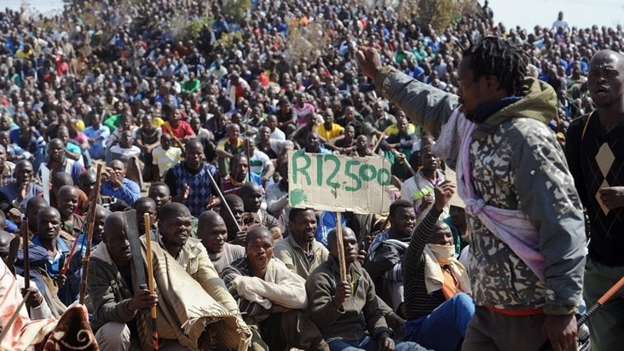 Miners sit together during a strike calling for increased wages, at a platinum mine in Marikana on August 16, 2012. Lawyers for relatives of 34 miners gunned down by South African police nearly a year ago said Wednesday they had pulled out of an already-troubled investigation into the deaths.