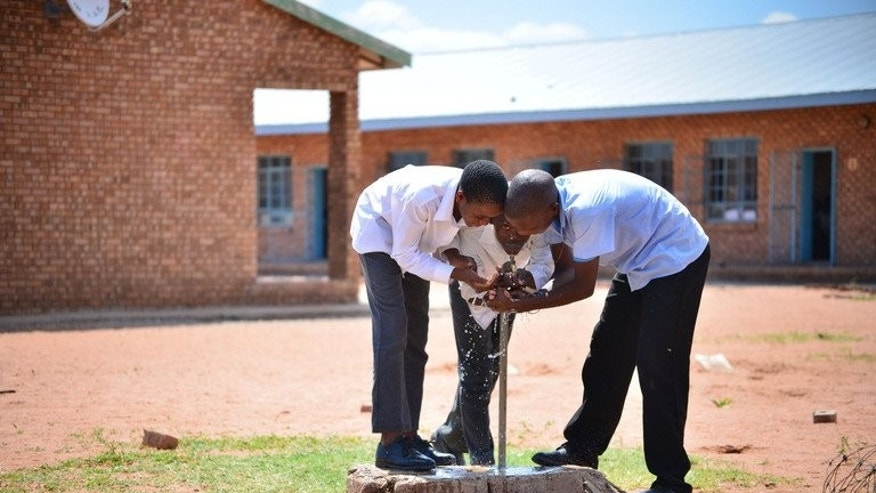 Students drink water at a well at the Alapha Secondary School, South Africa, on February 7, 2013. There is little shade or airconditioning to offer respite from the brutal heat.