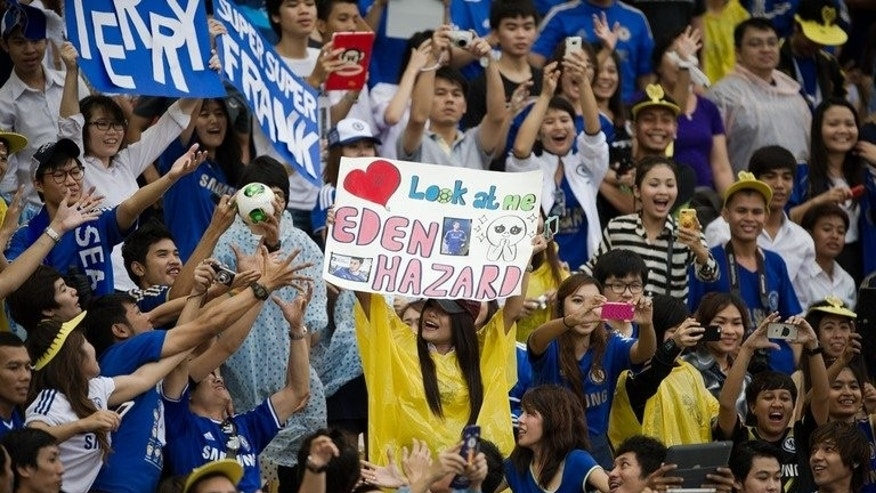 Chelsea fans cheer during a training session at the Rajamangala stadium in Bangkok, on July 16, 2013. Thailand has denied a father's claim that a boy chosen as a mascot for English giants Chelsea had been forced to make way for the prime minister's football-mad son.