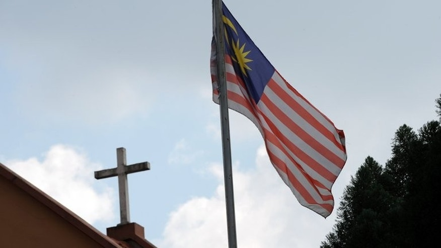 "The Malaysian national flag is shown near a Catholic Church in Kuala Lumpur on January 12, 2010. The Vatican's first-ever envoy to Malaysia has apologised for supporting the use of the word ""Allah"" by non-Muslims after he was summoned by the foreign minister."