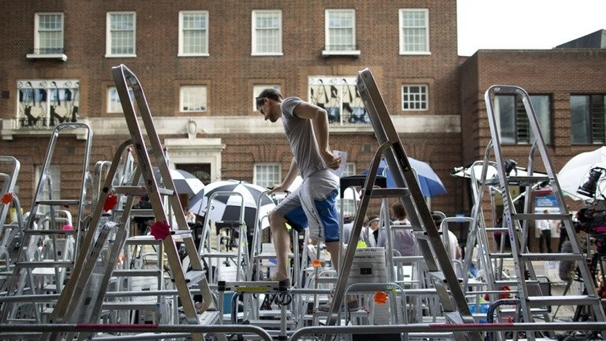 A press photographer climbs over ladders to look at his position outside the Lindo Wing of Saint Mary's Hospital in London, on July 17, 2013. In the general excitement surrounding the imminent arrival of a future British monarch, it is easy to forget the country's minority of republicans calling for an end to royal privilege.