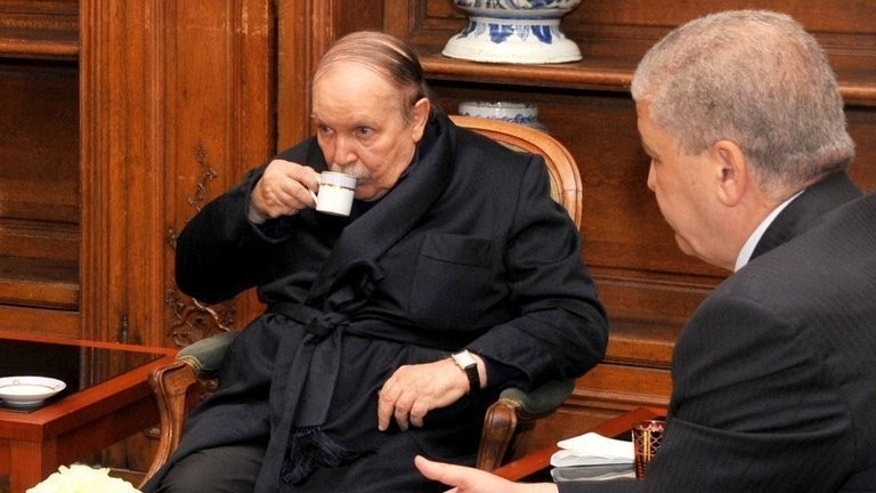 Algeria's President Abdelaziz Bouteflika (C) drinks tea with Prime Minister Abdelmalek Sellal in Paris on June 11. Bouteflika's return home after almost three months in hospital in Paris raises questions about his ability to complete the last nine months of his term, commentators say.