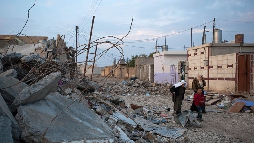 Syrians walk past destroyed buildings in the border town of Ras al-Ain, on November 26, 2012. At least 29 people have been killed in fighting between Kurdish and jihadist fighters in northern Syria in the past two days, according to the Syrian Observatory for Human Rights.