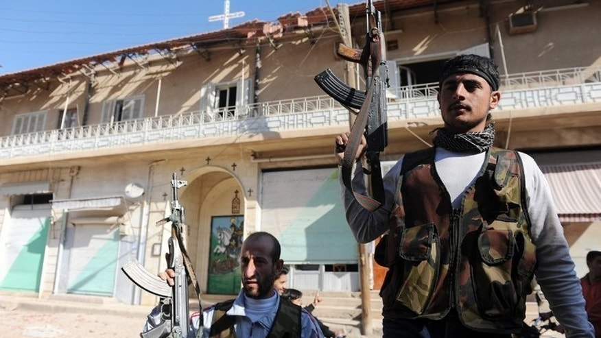 Syrian rebels stand guard outside a church in the town of Ras al-Ain, near the border with Turkey, on November 16, 2012. At least 29 people have been killed in fighting between Kurdish and jihadist fighters in northern Syria in the past two days, according to the Syrian Observatory for Human Rights.