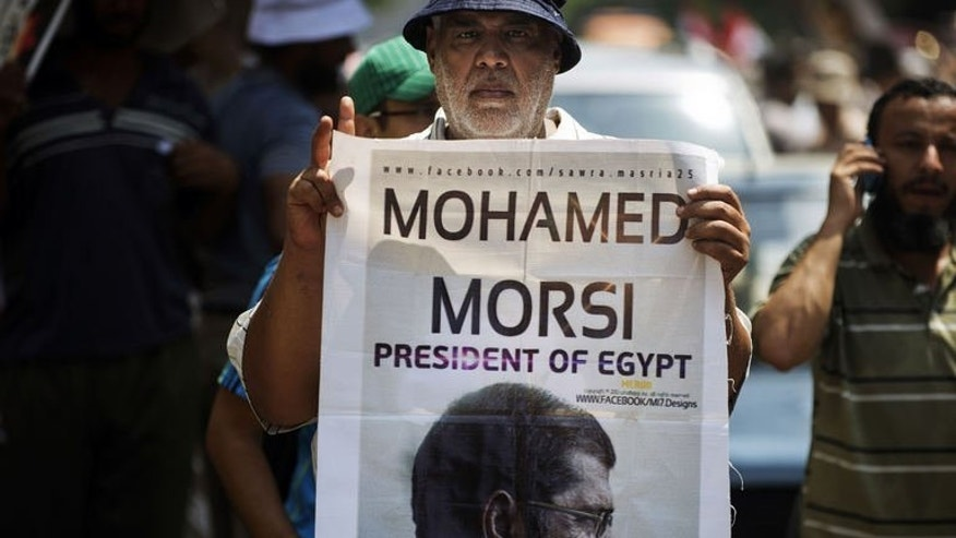 A man holds a portrait of ousted president Mohamed Morsi as thousands of his supporters demonstrate close to Egyptian cabinet headquarters on July 17, 2013 in Cairo. Egypt's Muslim Brotherhood Thursday slammed the European Union's failure to denounce the military coup that ousted president Mohamed Morsi, after the bloc's foreign policy chief met Islamist officials and called for his release.