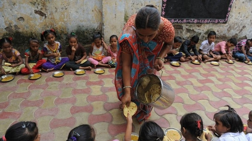 Indian schoolchildren are served a free mid-day meal in Ahmedabad on July 17, 2013. India's state governments run the world's largest school feeding programme involving 120 million children. Educators see it as a way to increase school attendance, in a country where almost half of all young children are undernourished.