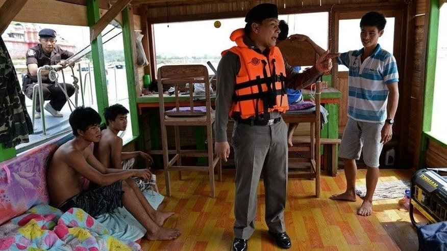 Thai Marine Border Police speak to the Laotian crew of a boat during a search of the vessel on the Mekong river, May 28, 2013. A dedicated Thai unit of 30 policemen, with three boats, now patrols a 17-kilometre (11 mile) stretch of the river border.