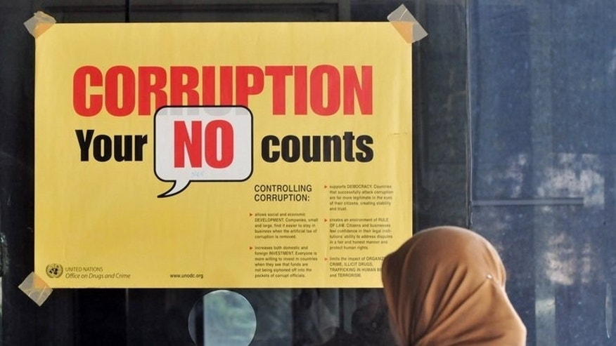 A woman stands next to an anti-corruption campaign banner at a corruption court in Jakarta on July 1, 2009. An Indonesian anti-corruption court Thursday jailed a second employee of the local subsidiary of US energy giant Chevron Corporation, in a case that has alarmed foreign investors.