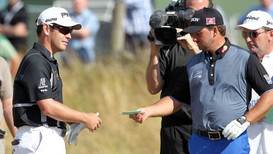 Northern Ireland's Graeme McDowell (R) gives the score card to South Africa's Louis Oosthuizen as the latter withdraws from competition during the first round of the 2013 British Open Golf Championship at Muirfield golf course at Gullane in Scotland on July 18, 2013.