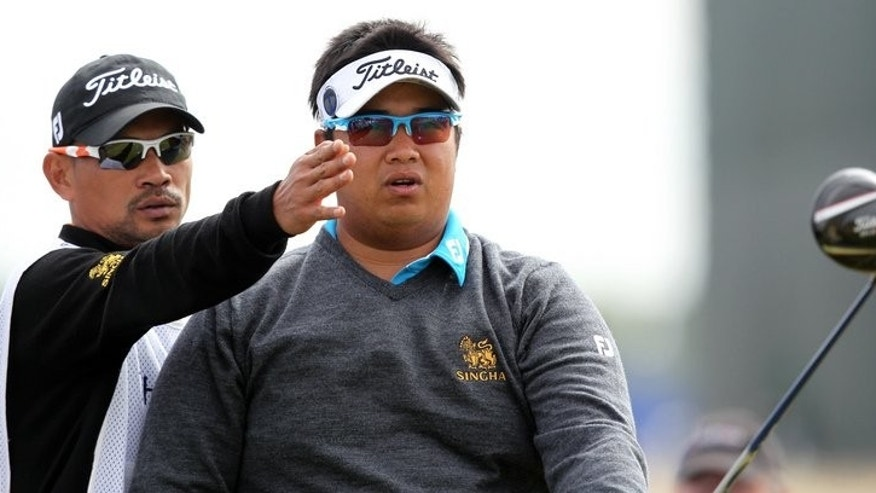 Thailand's Kiradech Aphibarnrat listens to his caddie before playing the 15th tee during the first round of the British Open at Muirfield golf course at Gullane in Scotland, on July 18, 2013. Kiradech battled to a one-over-par 72 after struggling with poor iron-play in the opening round of the British Open.