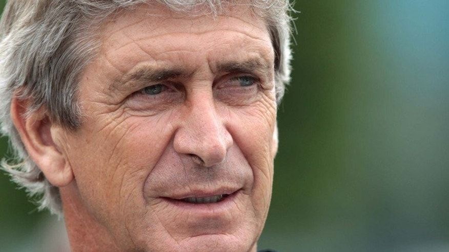 Manchester City's new manager, Manuel Pellegrini, arrives for a photocall at their training complex in Carrington, north west England, on July 10, 2013. Pellegrini could rejoin the squad in Hong Kong on Tuesday, according to assistant manager Brian Kidd. Pellegrini left City's pre-season training camp in South Africa and returned to his homeland of Chile due to a personal issue.