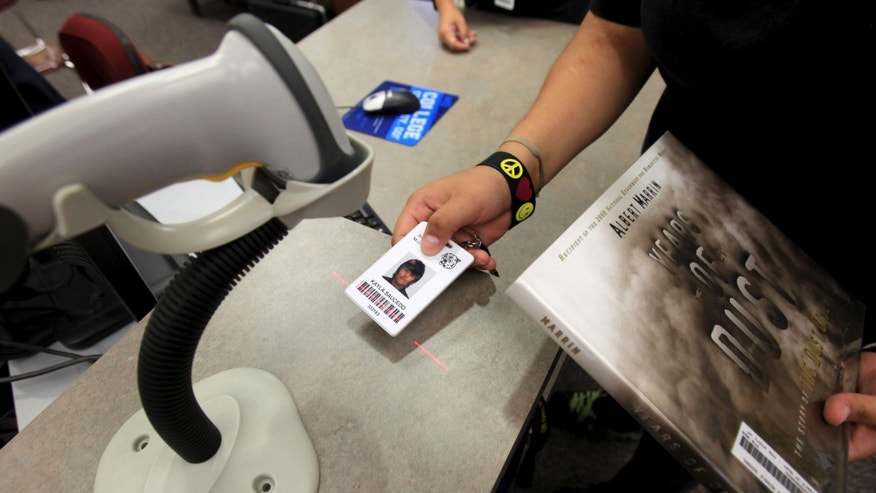 In this Oct. 1, 2012 photo, Kayla Saucedo, an 8th grader at Anson Jones Middle School, uses her new ID card to check out a book in the library in San Antonio, Texas.  (AP Photo/San Antonio Express-News, Bob Owen)