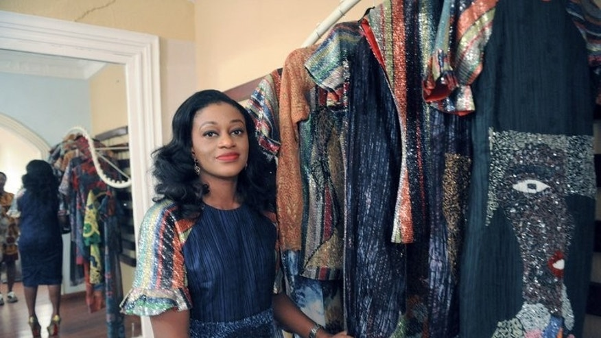 Designer and owner of LDA fashions, Lanre Da Silva Ajayi, stands beside her creations made with local fabrics, in Lagos, on June 14, 2013. A growing number of boutique owners and designers are working to change the fashion scene in Nigeria.
