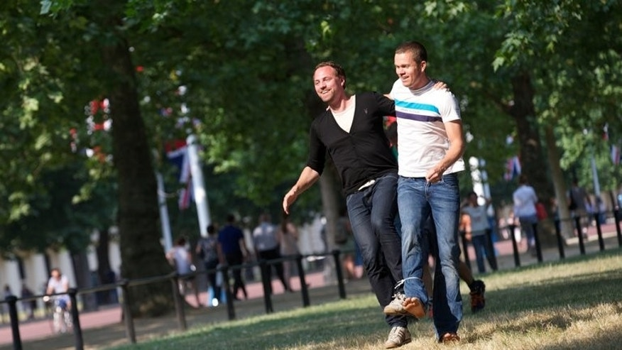"Two men take part in a three-legged race on a sunny day at St James's Park in central London on July 17, 2013. Britain was sweltering Thursday in its first prolonged heatwave in seven years as the deputy prime minister warned the country was simply ""not ready for this""."