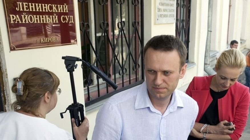 Russia's top opposition leader Alexei Navalny and his wife Yulia leave court in Kirov on July 5, 2013. The court on Thursday convicted Navalny of embezzlement in a case that could see President Vladimir Putin's top foe jailed for several years.