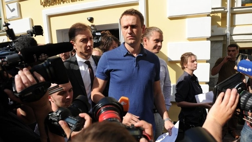Russia's top opposition figure Alexei Navalny addresses journalists and supporters after visiting the city's election commission office July 10, 2013, to register as a mayoral candidate in Moscow. A Russian court on Thursday convicted Navalny of embezzlement, in a verdict that will disqualify one of President Vladimir Putin's fiercest critics from politics and could see him jailed for years