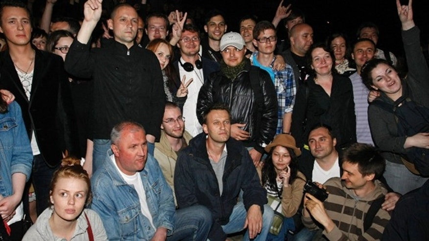 May 8, 2012: Alexei Navalny, at bottom center, a prominent anti-corruption whistle blower and blogger, and opposition leader Sergei Udaltsov, standing at second from left, pose with protesters gathering in the opposite side of the Presidential administrations building in downtown Moscow early Tuesday, a day after Vladimir Putin's inauguration.