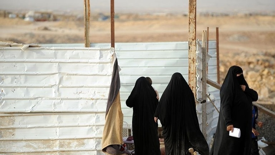 Stateless women stand at a makeshift home in a poor neighbourhood, east of the Saudi capital of Riyadh, on July 10, 2013. Born of tribal origin in Saudi Arabia, stateless people known as bidoons live on society's margins, unable even to register marriages or open a bank account because they lack identification cards.