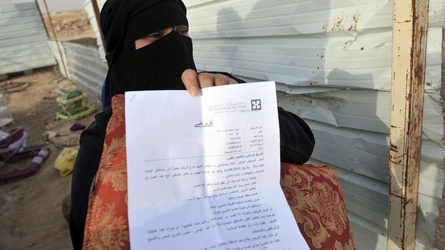 A stateless woman shows a medical report of her sick son at their makeshift shelter in an impoverished neighborhood east of the Saudi capital Riyadh on July 10, 2013. The bidoons have long been marginalised and are not entitled to state-provided services and benefits.