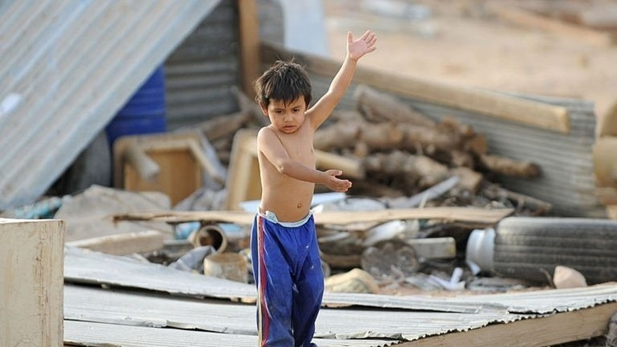 The child of a stateless family plays outside his makeshift home in an impoverished neighbourhood, east of the Saudi capital of Riyadh, on July 10, 2013. The stateless nomads, known as bidoons, were originally traveling between Saudi Arabia, Iraq, Kuwait and Jordan.