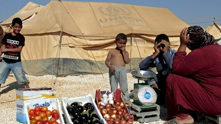 A Syrian refugee woman sells vegetables at the Zaatari refugee camp near the border with Syria on January 3, 2013.